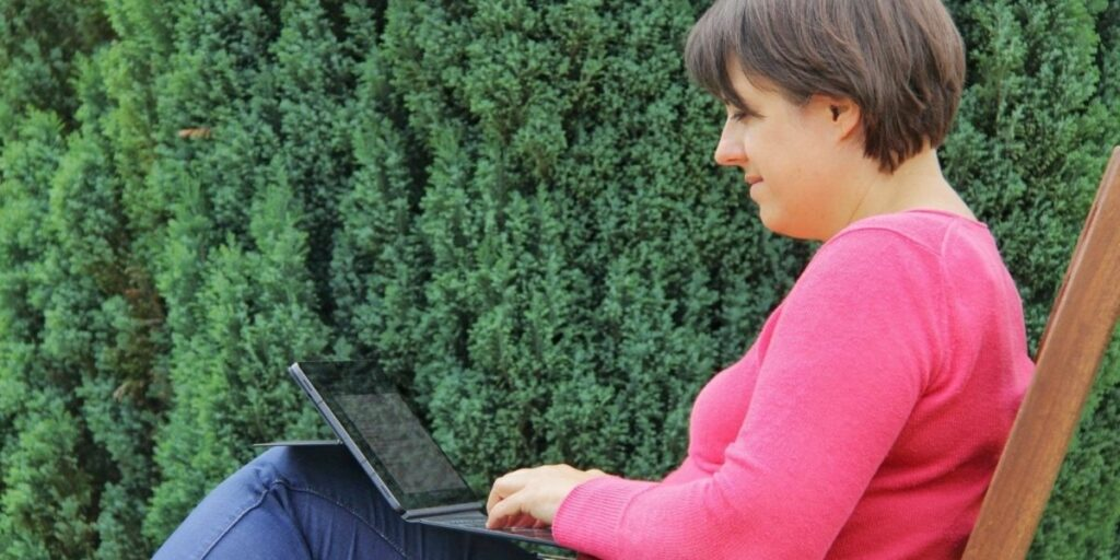 Carolin Gärtner sitzt mit dem Tablet im Garten und blogt