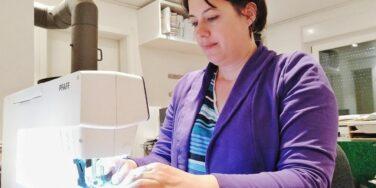 Carolin Gärtner sitzt an der Nähmaschine und näht