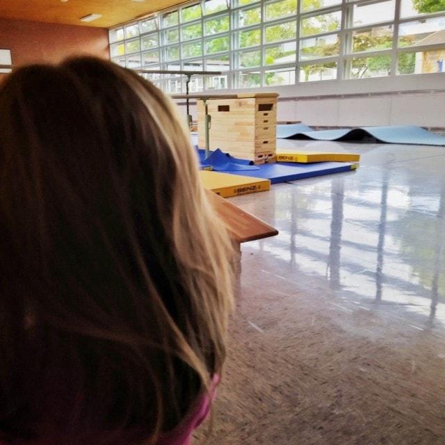 Unsere Kleine steht in der Turnhalle und schaut sich die aufgebauten Geräte an.