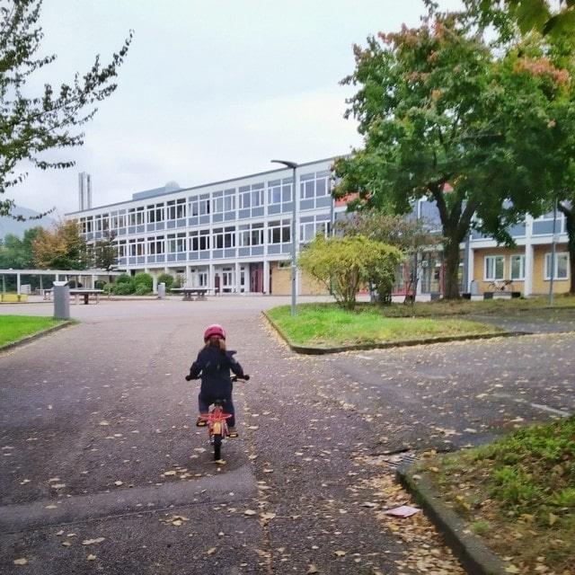 Unsere Kleine ist mit dem Fahrrad auf dem Weg zum Schulhof